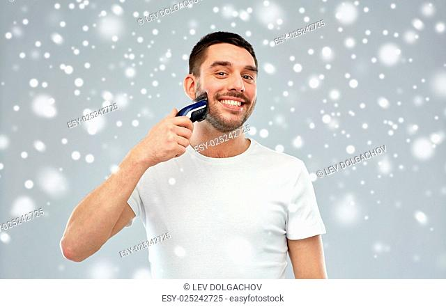 beauty, grooming, winter, christmas and people concept - smiling young man shaving beard with trimmer or electric shaver over snow on gray background
