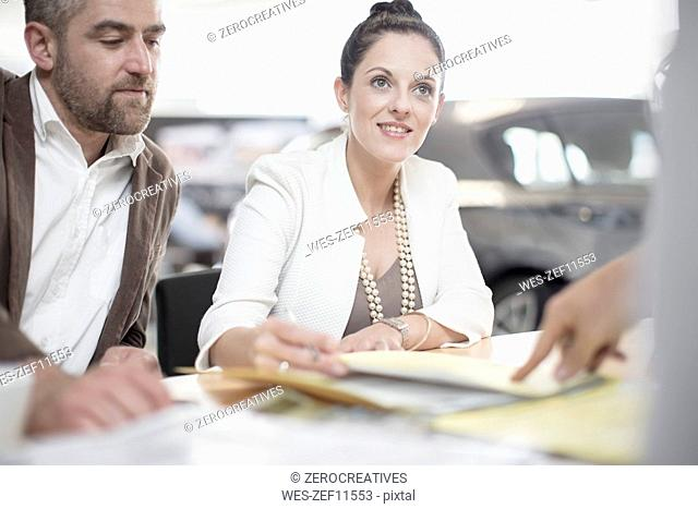 Car dealer and couple sitting at desk with agreement forms in showroom