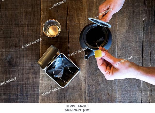 High angle close up of person adding tea bag to small black tea pot