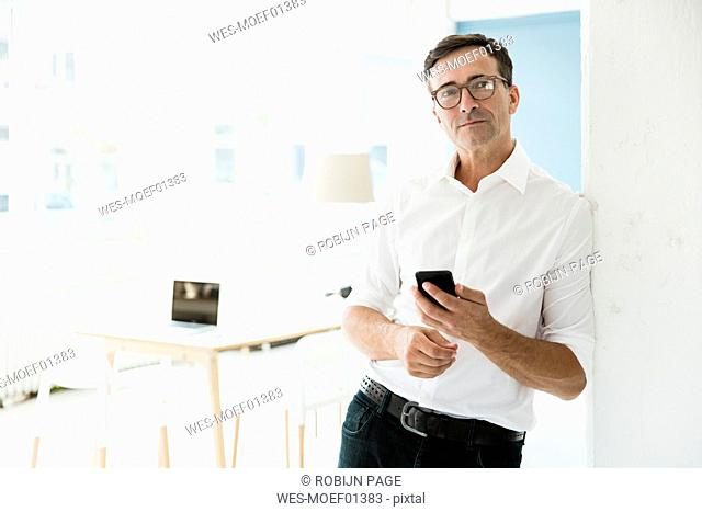 Businessman with cell phone in bright office