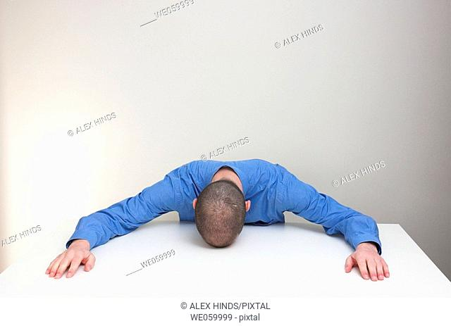 Young man in business slumped over an empty desk. Body language suggests exhaustion, defeat, exasperation etc