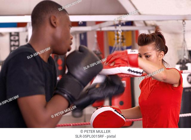 Boxer training with coach in gym