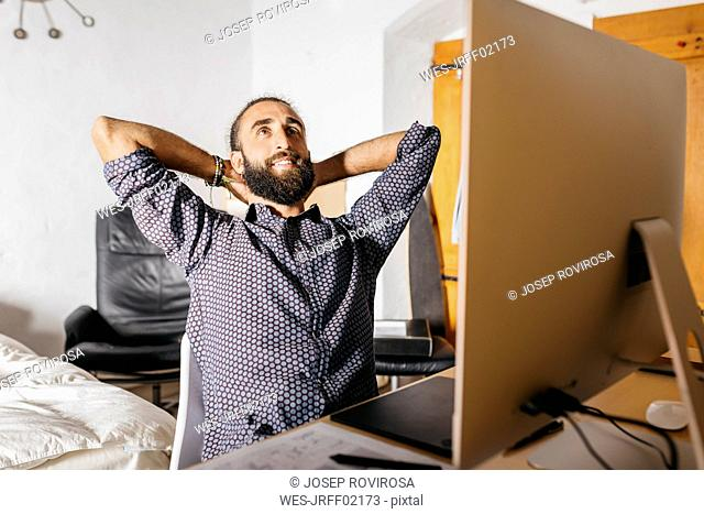 Smiling young man working relaxed at home