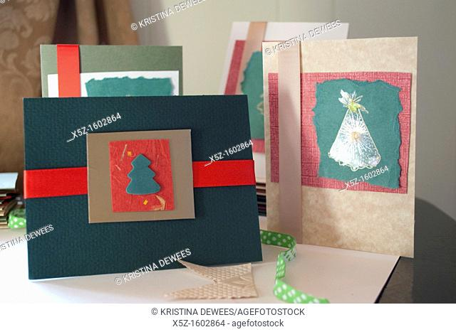 Some homemade Christmas cards made with ribbons, stickers and various papers