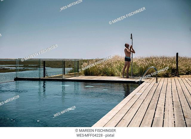 Man taking a shower on the edge of a modern infinity swimming pool