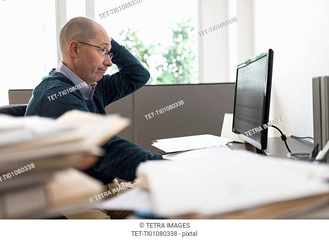 Surprised mature businessman looking at computer monitor