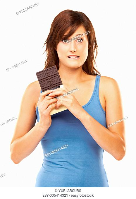 Studio portrait of a tempted-looking young woman holding a huge bar of chocolate isolated on white