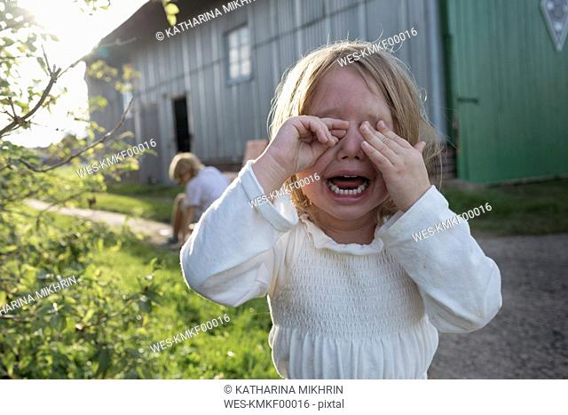 Portrait of screaming little girl covering eyes with her hands