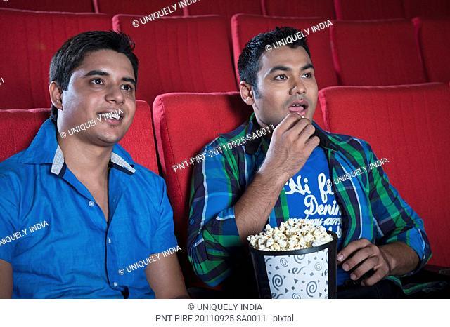 Friends enjoying movie with popcorns in a cinema hall