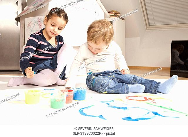 Girl and boy playing with finger paint