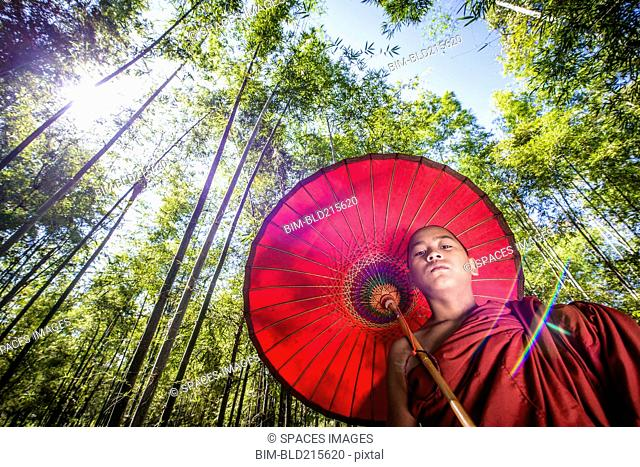 Low angle view of Asian monk-in-training under parasol in forest