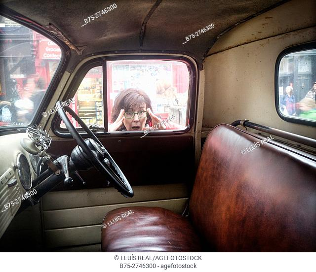 Interior view of vintage car. Steering wheel. Purple seats. Woman looking through the window with surprised expression. England