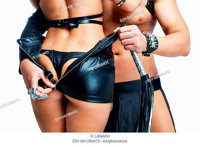 two young striptease dancers wearing leather isolated against white studio background