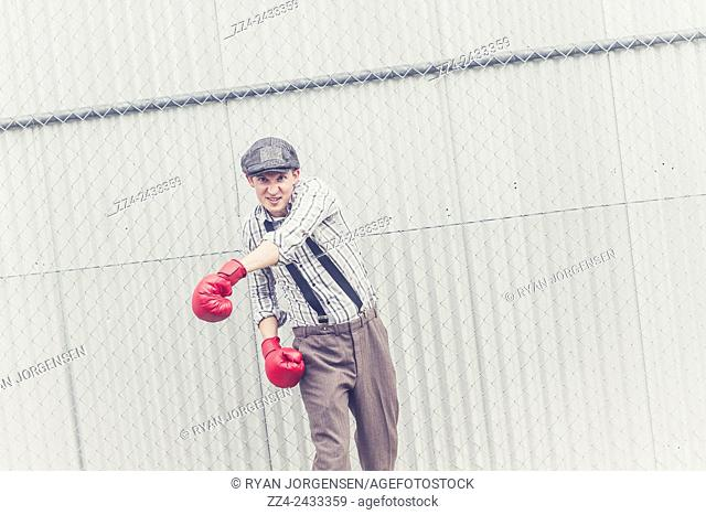 Vintage toned image of a young male boxer throwing a power jab when raising his fists in an offensive attack. Vintage power and passion