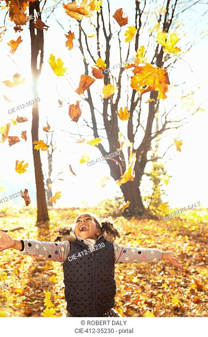 Playful girl throwing leaves overhead in sunny autumn park