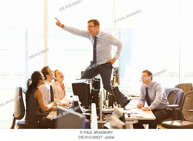 Laughing colleagues watching exuberant businessman dancing on top of desks in office