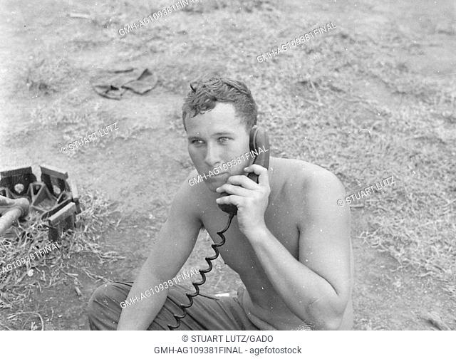 A shirtless United States soldier sits on the ground and speaks on a portable radio during the Vietnam War, Vietnam, 1966