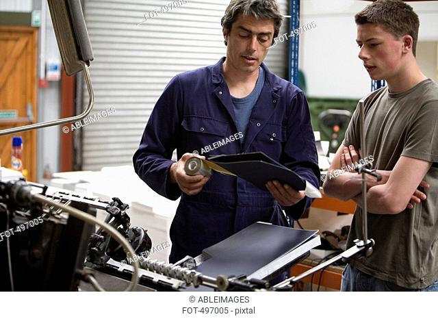 A man training a young man in a printing factory