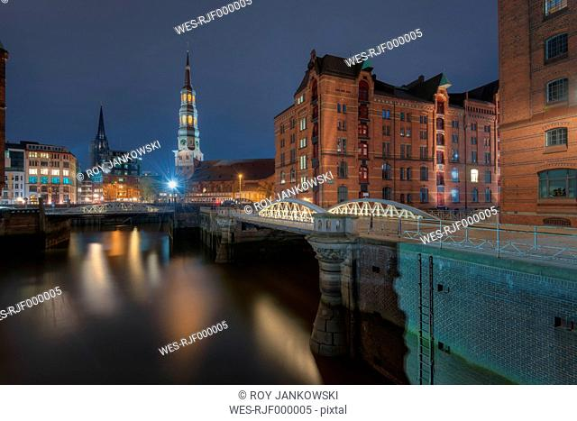 Germany, Hamburg, old warehouse district (Speicherstadt) with St Catherine's church at background by night