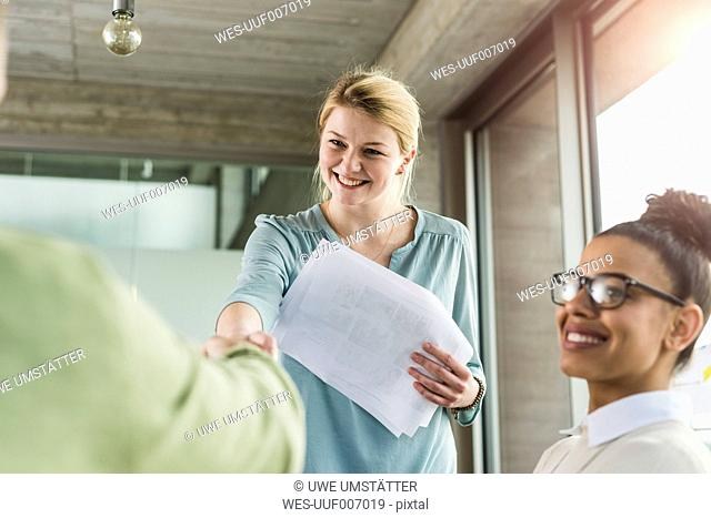 Young woman in office shaking hands with colleague