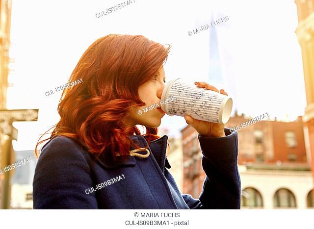 Young female tourist drinking coffee on street, Manhattan, New York, USA