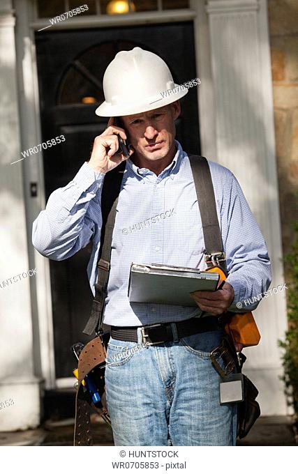 Cable installer leaving home after completing work order and talking on a cell phone