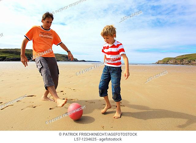 father and son playing football on beach, Sutherland, Scotland
