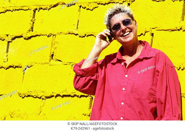 Woman talking on phone against wall