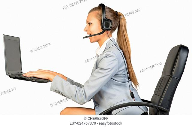 Businesswoman in headset sitting on office chair, typing on laptop with blank screen, smiling. Isolated over white background