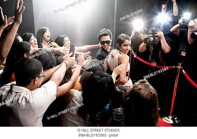 Celebrities posing on red carpet