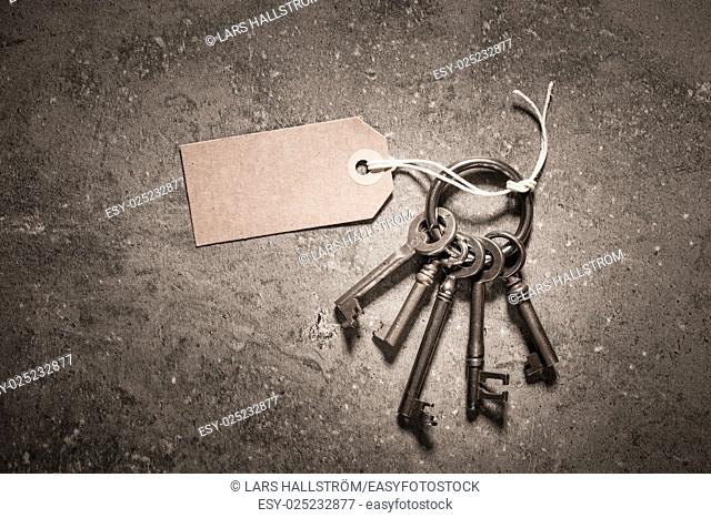 Vintage key set with blank paper tag on stone table. Symbol of nostalgia, security and access