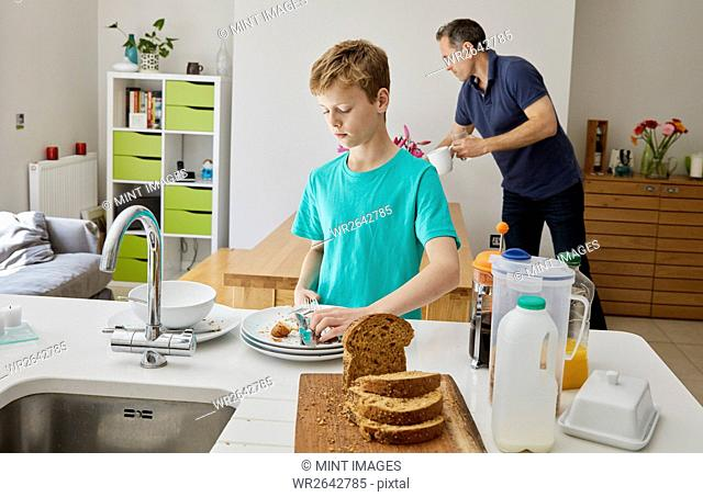 A family home. A man and a boy clearing away plates after breakfast