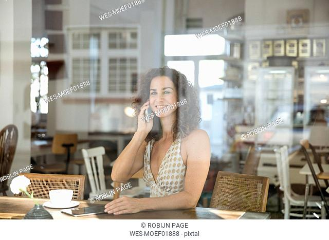 Mature woman sitting in coffee shop, talking on the phone