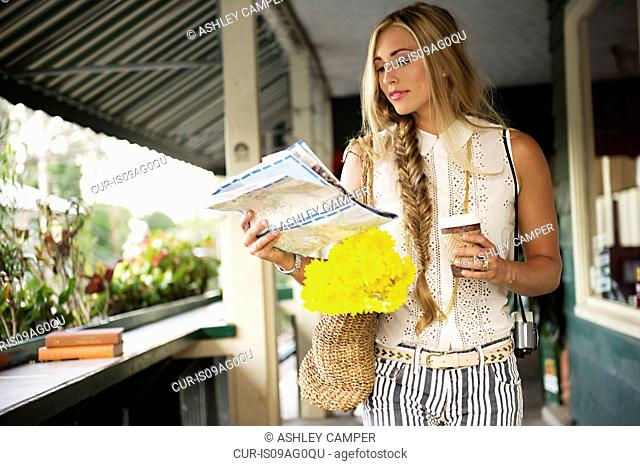 Young woman with map in verandah