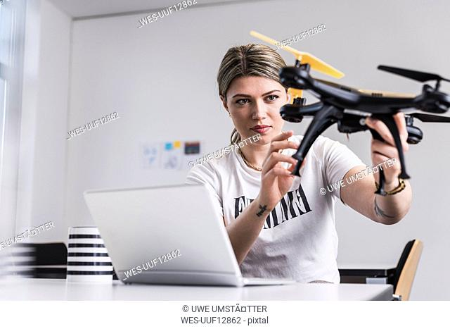 Young woman with laptop at desk holding drone
