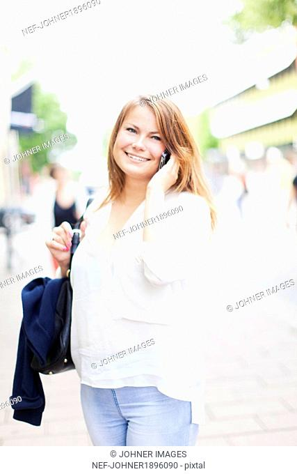 Smiling young woman talking via cell phone, Vaxjo, Smaland, Sweden