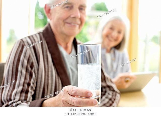 Older man taking medication in water