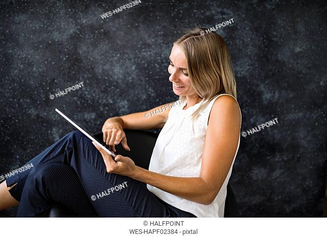 Smiling businesswoman sitting in armchair using tablet