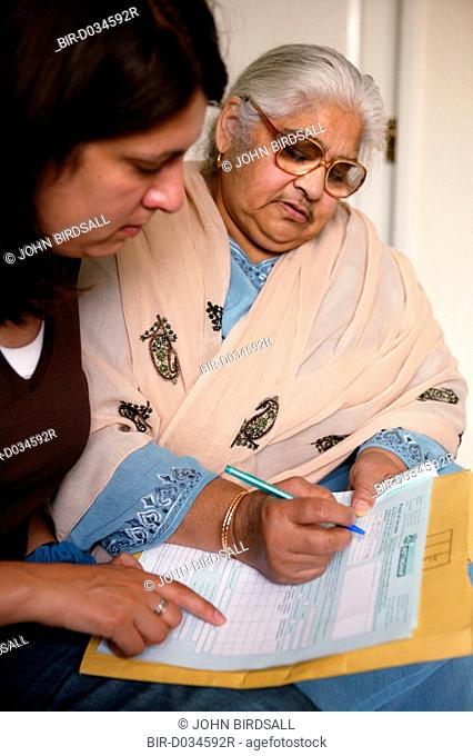Community support worker helping South Asian lady fill in a form
