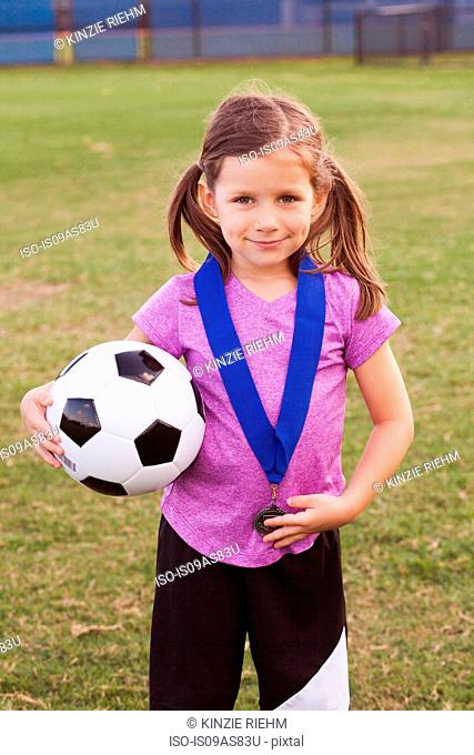 Portrait of girl football player with medal on practice pitch