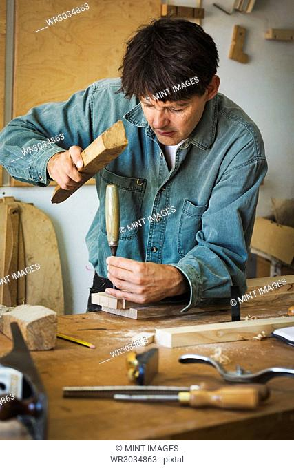 A craftsman using a piece of wood on the end of a chisel to mark a piece of wood