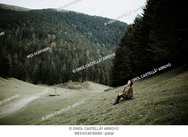 Young woman sitting on a meadow near forest edge looking up