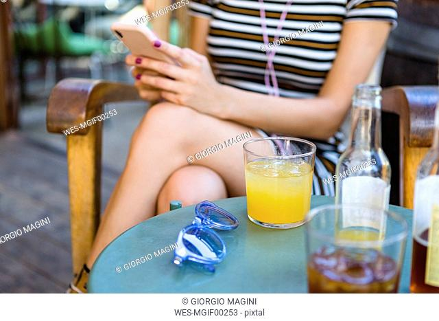 Young woman relaxing at pavement cafe having soft drinks
