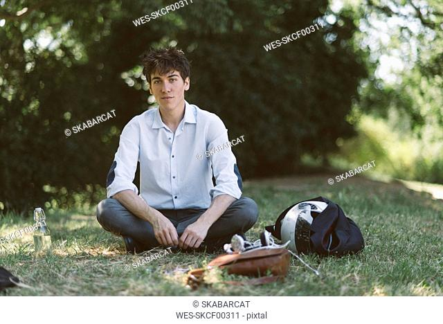 Portrait of young man sitting on meadow in park