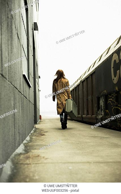 Young woman with suitcase on platform