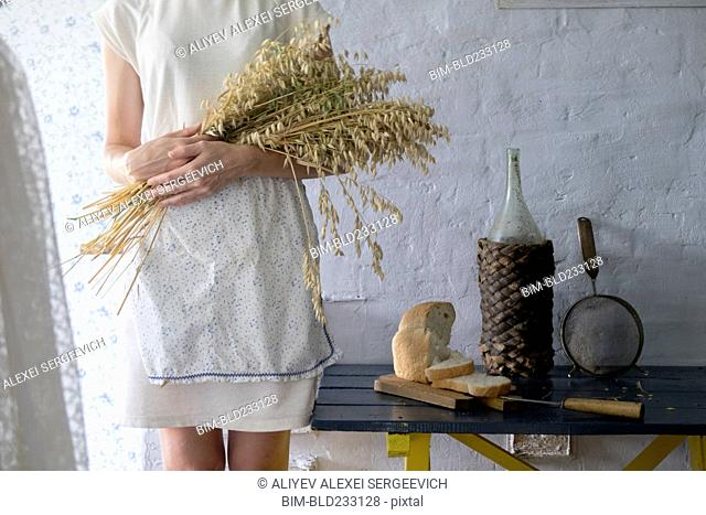 Caucasian woman holding bouquet of wheat near sliced bread