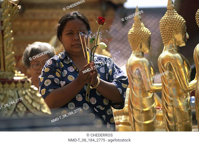 Mid adult woman praying in a temple, Thailand