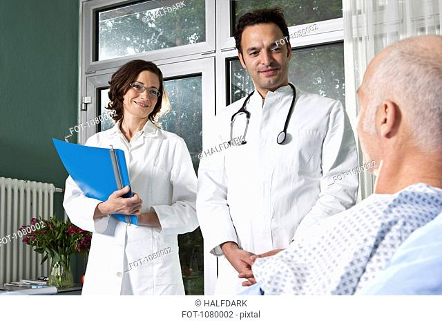 Two doctors next to a male patient in a hospital ward
