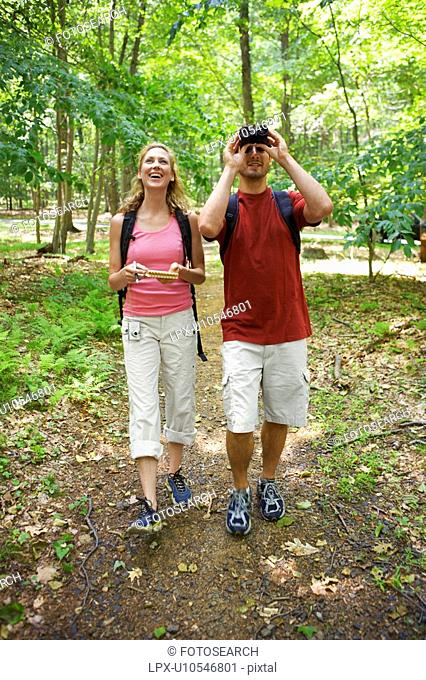 Man and woman watching birds in forest