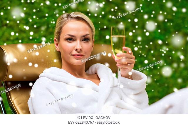 people, beauty, lifestyle, holidays and relaxation concept - beautiful young woman in white bath robe lying on chaise-longue and drinking champagne at spa with...